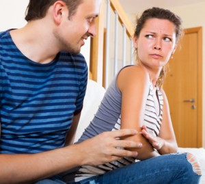 Partner asking sad another for forgiveness in living room